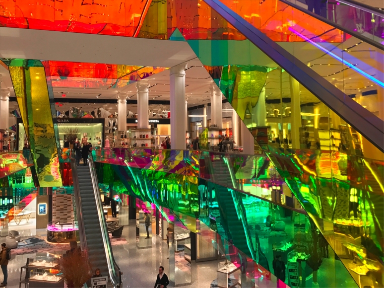 Designed by Rem Koolhaas, the new dichroic film-coated escalators at Saks not only twinkle, but also throw flashes of color on the white walls and columns. (Photo by Theadora Brack)